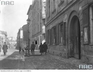 Opis obrazu: Fragment ulicy w kierunku północnym z budynkiem pod numerem 22  (pierwszy z prawej). Widoczni przechodnie. NAC